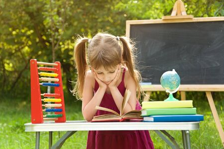 Girl learns lessons in nature. she is reading an interesting book Stock Photo