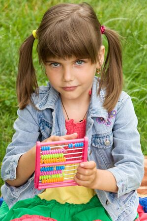 small smart schoolgirl counts on the abacus Stock Photo