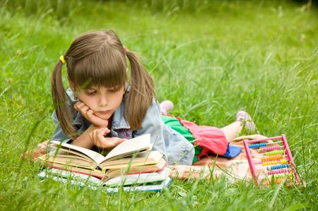 generosidad: inteligente pequeña alumno lee un libro Foto de archivo