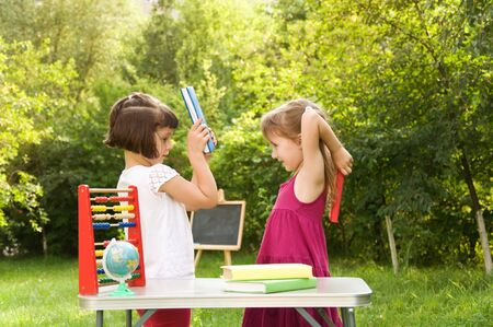 fracas: Two school girls quarrel and fight with books Stock Photo