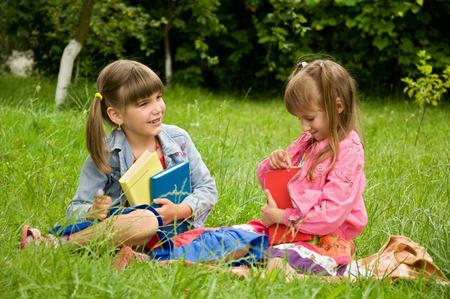 generosidad: Las niñas la lectura de libros en el césped y decirnos algo interesante