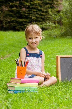 generosidad: pequeña colegiala preparándose para la escuela en la naturaleza. el desarrollo de la primera infancia