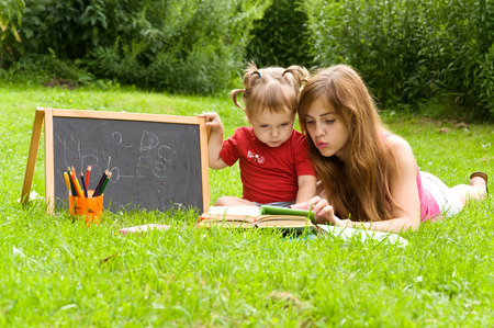 teaches: mother teaches her young child letters. Early child development Stock Photo