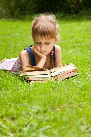 generosidad: La pequeña colegiala está leyendo un libro. pequeña alumna inteligente Foto de archivo