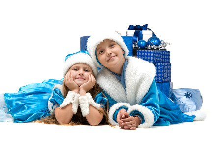 generosidad: small child in costume lie on the floor with a gift. Merry Christmas