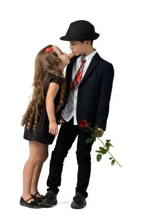 relationship between young children. boy gives a girl flowers. boy kisses a girl Stock Photo