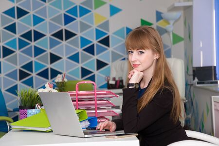prestigious: young beautiful successful woman is a prestigious job in the office. comfortable conditions