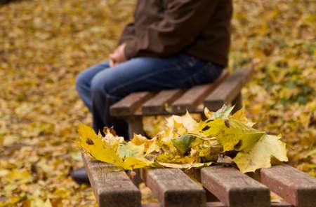 elderly man sitting alone on a park bench. autumn