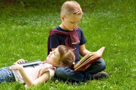 generosidad: Little school children read a book in nature. Smart little pupil. Early development of children. Training and rest Foto de archivo