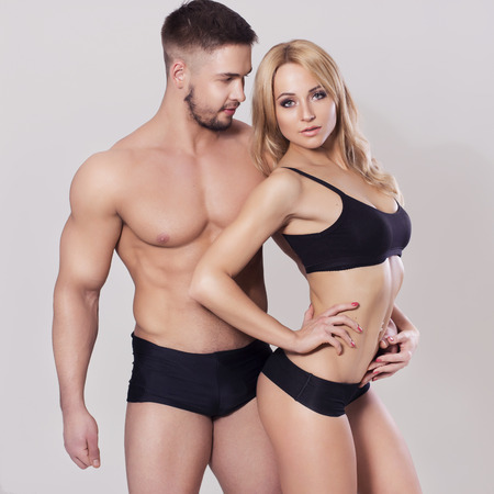 muscle belly: Sexy fit muscled couple in sportswear on neutral grey background hugging Stock Photo