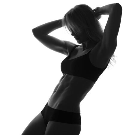 musculo: Cuerpo en forma delgada atractiva mujer. Abdomen musculoso. Ropa de deporte. Aislado en blanco. Imagen en blanco y negro