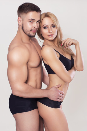 black woman white man: Sexy fit muscled couple in sportswear on neutral grey background hugging Stock Photo