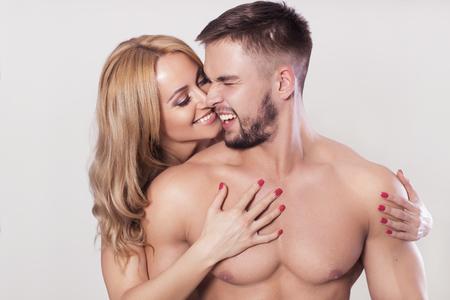 abdominal fitness: Ajuste musculoso atractivo pareja en ropa deportiva en el fondo gris neutro abrazos Foto de archivo