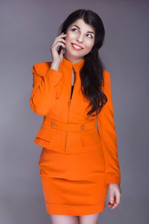 buisness: Beautiful brunette caucasian woman in orange stylish buisness suit talking on the phone. grey neutral background