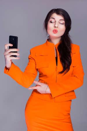 buisness woman: Beautiful brunette caucasian woman in orange stylish buisness suit make selfie on the phone. grey neutral background