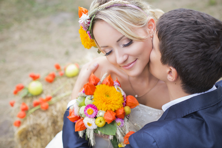 the groom: Young couple in wedding gown. Bride holding bouquet of flowers.