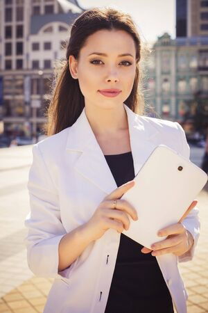 disposer: Beautiful brunette business woman in white suit working on a tablet in her hands outdoors