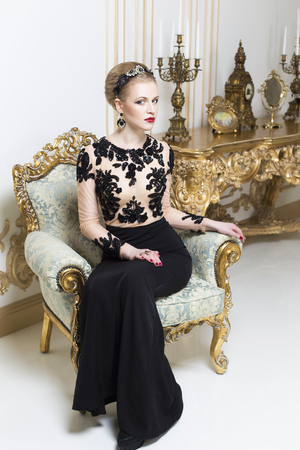 sequins: Beautiful blonde royal woman sitting on a retro chair in gorgeous luxury dress, looking at camera. Indoor