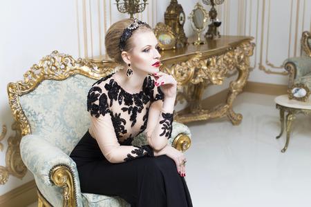 Bella donna bionda reale, seduta su una sedia retrò in abito di lusso splendido. Interno. Copy Space