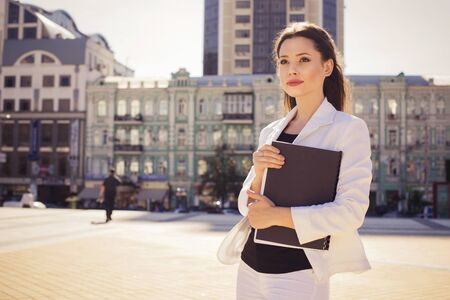disposer: Beautiful brunette business woman in white suit with folder of documents in her hands outdoors. copy space