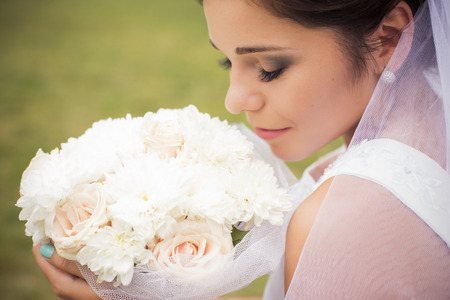 Beautiful bride preparing to get married in white dress and veil with bouquet of roses in the park alone. outdoors. copy space Stok Fotoğraf