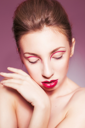 Beautiful brunette woman with red full lips and red lines on her eyelids and braid hairstyle