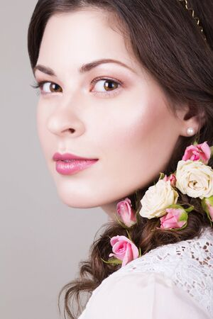 Beautiful brunette bride smiling with natural make up and flowers roses in her hairstyle and looking sideways