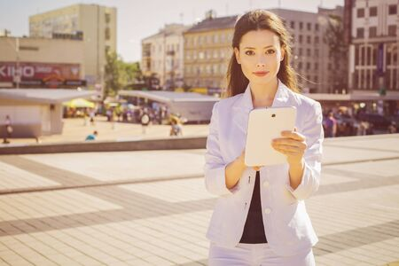Beautiful brunette business woman in white suit working on a tablet in her hands outdoors. copy space