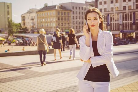 Beautiful brunette business woman in white suit and black t-shirt talking on a cell phone outdoors