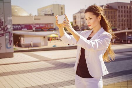 Beautiful brunette business woman in white suit photographing selfie on a tablet in her hands outdoors. copy space Standard-Bild