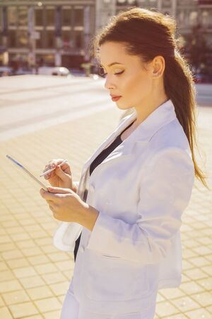 Beautiful brunette business woman in white suit working on a tablet in her hands outdoors