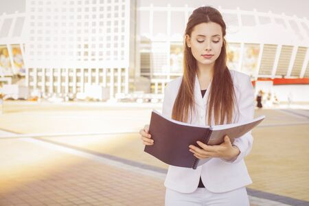 Beautiful brunette business woman in white suit with folder of documents in her hands outdoors. copy space