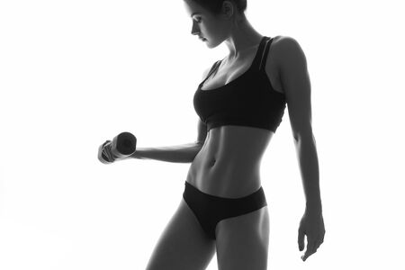 Sexy slim fit woman body with dumbbells. Muscled abdomen. Sportswear. Isolated on white. Black and white image Stock Photo