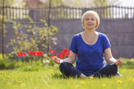 Beautiful blonde eldery senior woman relaxing on a grass in park in yoga meditation. casual outfit. copy space