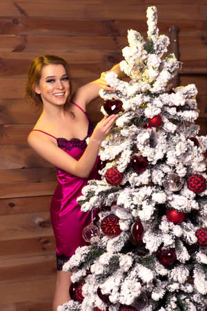 Cute brunette caucasian woman in underwear red dress at evening in her home cozy interior room near new year tree on a christmas eve, with presents near her. Smiling cheerfully