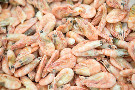 Frozen seafood in ice at supermarket: shrimps