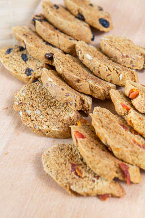 Homemade tasty biscotti with raisins and dried fruits. Italian traditional receipt. Healthy no sugar food. Wooden background Banque d'images