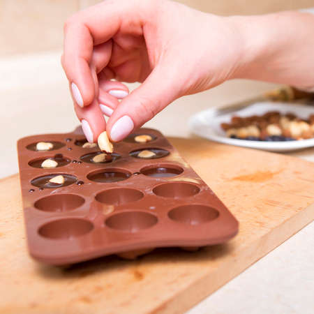 Woman preparing homemade no sugar proper nutrition chocolate candies on a wooden background. Healthy food