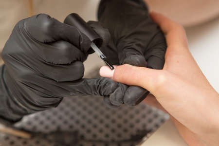 Nail master in rubber gloves apply gel polish shellac on a woman hand finger nail. Healthcare beauty cosmetic spa procedure in a salon