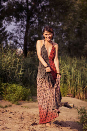 Brunette sexy cute woman in ethnic style bohemian boho hippie dress and jewelry in the park. Slim fit body. Sunny day, summer evening. Copy space Stockfoto