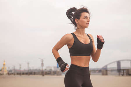 Brunette slim adult fit sporty caucasian woman in sportswear on a european city streets in morning do exercises (workout), stretch her legs and butt. Copy space