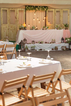 Simple but luxury rich table setting for a wedding celebration in nice cozy restaurant. Wineglasses, plates and bouquet of summer seasonal flowers on a table. Sunlight from a window. Copy space