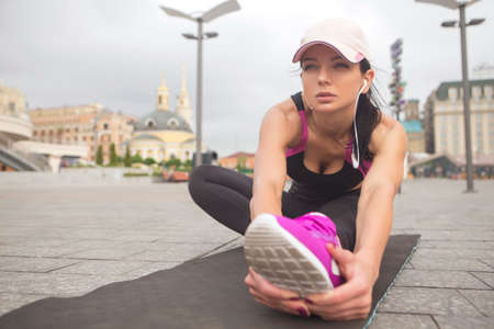 Brunette slim adult fit sporty caucasian woman in sportswear on a european city streets in morning do exercises (workout) - plank. Copy space