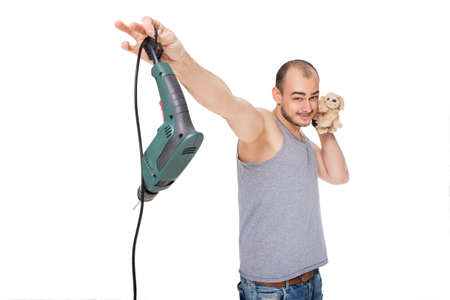Caucasian man is afraid of men's work, holding drill tool in disdain in one hand, and soft toy puppy in other hand (near his face, choosing puppy over drill). Casual clothes. Isolated on white