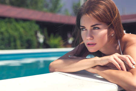 Beautiful brunette seductive rich luxury young woman with perfect slim fit body in black bikini standing near swimming pool with her back to camera. Fashion posing. Bright sunlight. Copy space
