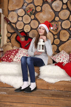 Girl in red Santa Claus hat sitting and smiling with white Stock Photo