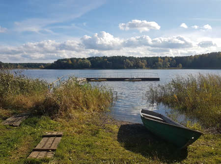 Large forest lake Yalchik in Mari El in Russia on a sunny autumn day, in the foreground a boat on the shore Stock Photo