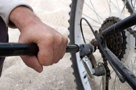 Men's hands pump up a bicycle wheel close-up