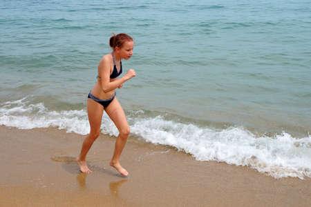 girl in a swimsuit runs along the sandy beach along the sea