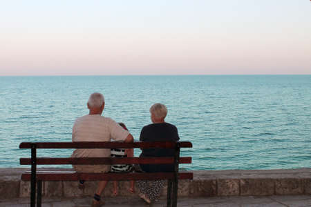 elderly couple sitting on a bench and looking at the sea